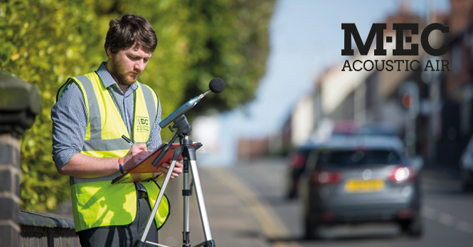noise engineer monitors road traffic noise levels at the side of a busy road